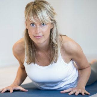 Billede af kvinde på yogamåtter der løfter sig op med armene